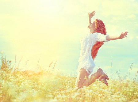 Foto de Beauty model girl in white dress jumping on summer field - Imagen libre de derechos