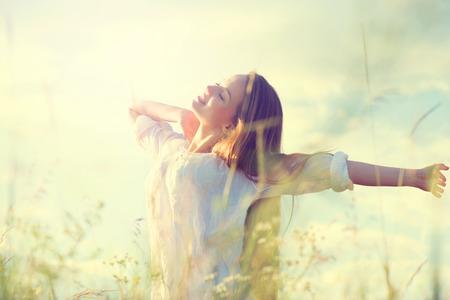 Foto de Teenage model girl in white dress having fun on summer field - Imagen libre de derechos