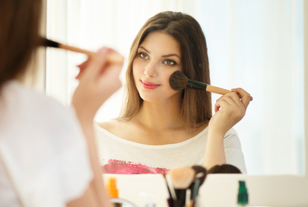 Photo for Beauty woman looking in the mirror and applying makeup - Royalty Free Image