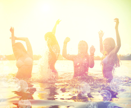 Photo for Group of happy teen girls playing at the beach on sunset - Royalty Free Image