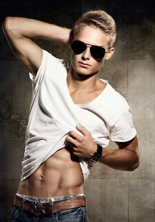 Photo pour Handsome young man  Cheerful sexy guy wearing sunglasses - image libre de droit
