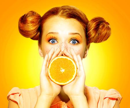 Girl takes juicy orange  Beauty joyful teen girl with freckles