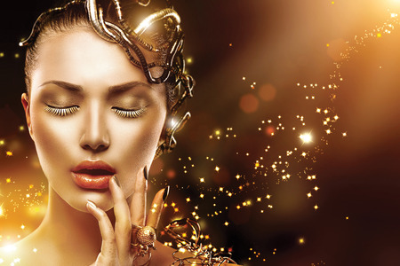 Photo pour Model woman face with gold skin, nails, make-up and accessories - image libre de droit