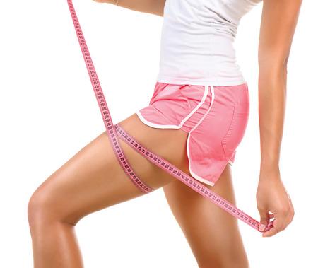 Foto de Sporty model girl measures her leg with a measuring tape - Imagen libre de derechos