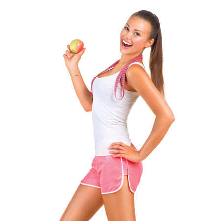 Photo for Sporty girl holding an apple while standing sideways - Royalty Free Image