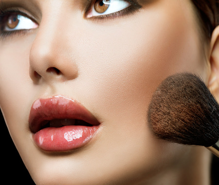 Foto de Makeup applying. Beautiful fashion model girl face closeup - Imagen libre de derechos
