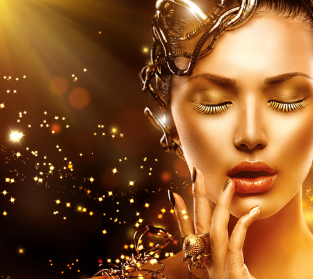 Foto de Model woman face with gold skin, nails, make-up and accessories - Imagen libre de derechos
