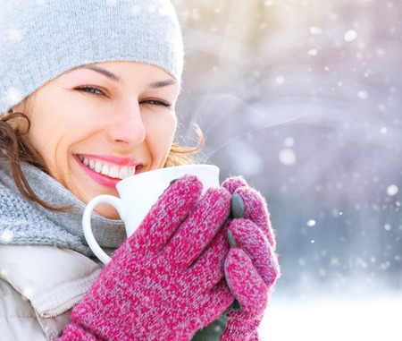 Foto de Beautiful happy smiling winter woman with hot drink outdoor - Imagen libre de derechos