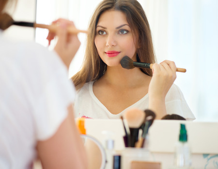 Photo pour Beautiful girl looking in the mirror and applying cosmetic - image libre de droit