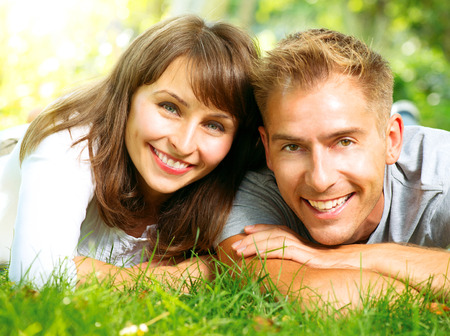Photo for Happy Smiling Couple Together Relaxing on Green Grass - Royalty Free Image