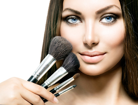 Beauty Girl with Makeup Brushes. Applying Makeup