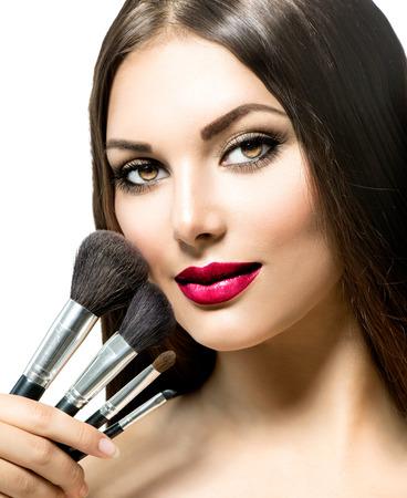 Photo pour Beauty Woman with Makeup Brushes. Applying Holiday Makeup - image libre de droit