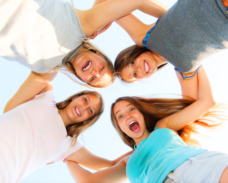 Photo for Group of smiling friends staying together over blue sky - Royalty Free Image