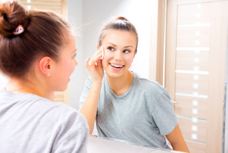 Photo pour Beauty teenage girl cleaning her face with cotton pad at home - image libre de droit