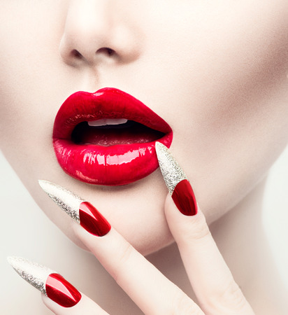 Photo pour Makeup and Manicure. Red Long Nails and Red Glossy Lips - image libre de droit