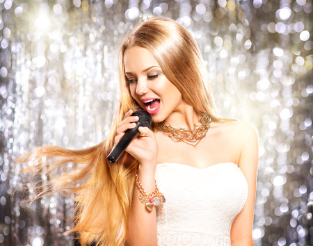 Photo for Beauty model girl with a microphone singing and dancing - Royalty Free Image