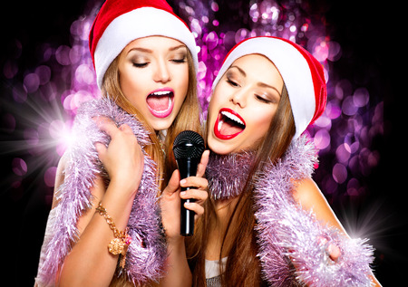 Photo for Christmas party, karaoke. Beauty girls in santa hats singing - Royalty Free Image