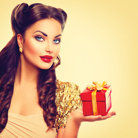 Photo pour Beauty pin up girl with holiday gift box in her hand - image libre de droit