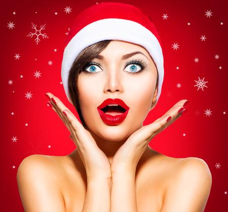 Foto de Christmas Surprised Winter Woman. Beauty Model Girl in Santa Hat - Imagen libre de derechos