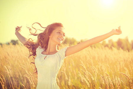 Foto de Beauty happy girl with blowing hair enjoying nature on the field - Imagen libre de derechos