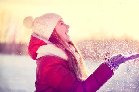 Foto de Beauty winter girl blowing snow in frosty park. Sunny day - Imagen libre de derechos