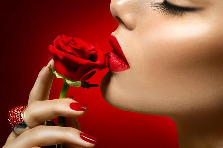Photo pour Beautiful model woman kissing red rose flower - image libre de droit