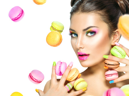 Photo pour Beauty fashion model girl taking colorful macaroons - image libre de droit
