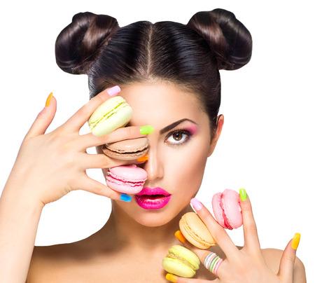 Photo pour Beauty fashion model girl taking colorful macaroons - image libre de droit