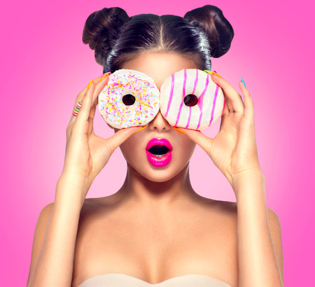 Foto de Beauty model girl taking colorful donuts. Dieting concept - Imagen libre de derechos
