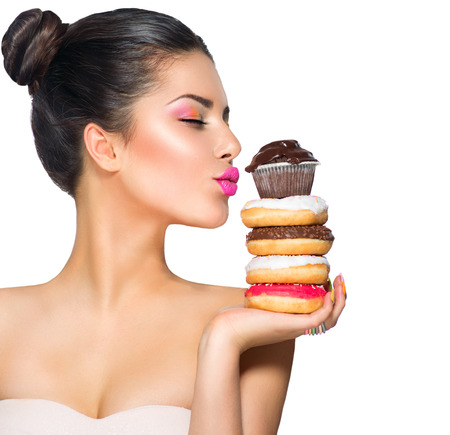 Foto de Beauty fashion model girl taking sweets and colorful donuts - Imagen libre de derechos