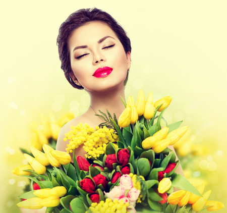 Foto de Beauty model woman with spring flower bouquet - Imagen libre de derechos