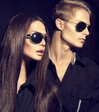 Photo pour Fashion models couple wearing sunglasses over dark background - image libre de droit