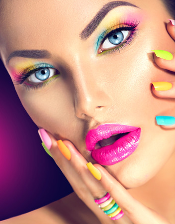 Photo pour Beauty girl face with vivid makeup and colorful nail polish - image libre de droit