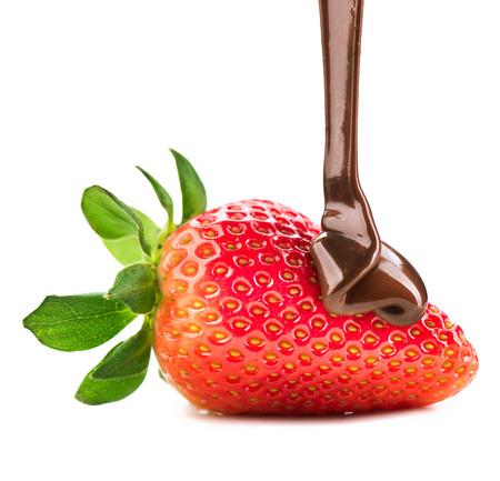 Foto de Melted chocolate pouring on fresh ripe juicy strawberry - Imagen libre de derechos