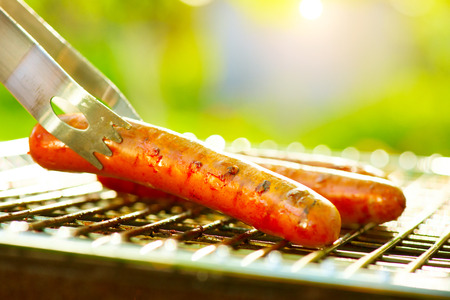 Photo for Grilled Sausage on the flaming Grill. Barbecue outdoors. BBQ - Royalty Free Image