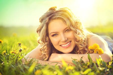 Photo pour Beautiful young woman lying on a field enjoying nature - image libre de droit