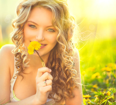 Photo pour Beauty blond model girl smelling dandelion flower - image libre de droit