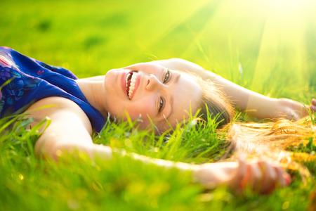 Foto de Beautiful young woman lying on the field in green grass - Imagen libre de derechos