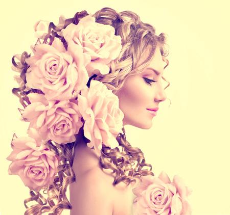 Foto de Beauty girl with rose flowers hairstyle. Long permed curly hair - Imagen libre de derechos
