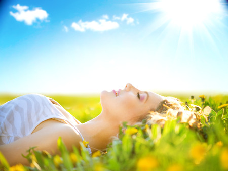 Foto de Beautiful healthy girl lying on summer field with flowers - Imagen libre de derechos