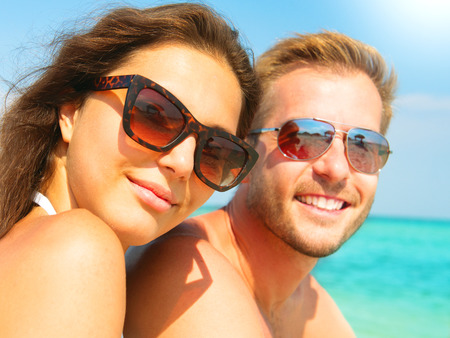Foto de Happy couple in sunglasses having fun on the beach - Imagen libre de derechos