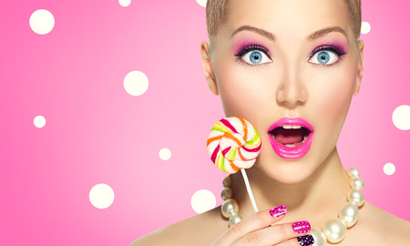 Photo for Funny girl holding lollipop over pink polka dots  - Royalty Free Image