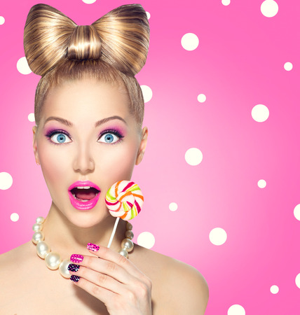 Photo pour Funny girl eating lollipop over pink polka dots  - image libre de droit