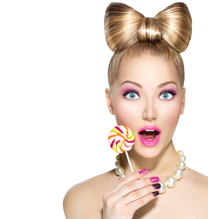 Foto de Funny girl with bow hairstyle eating colorful lollipop - Imagen libre de derechos