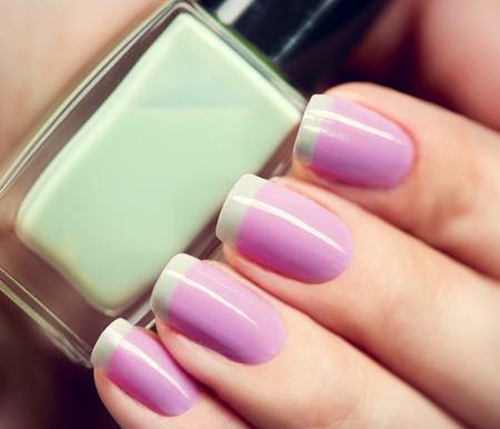 Photo pour Stylish colorful nails and nailpolish bottle closeup - image libre de droit