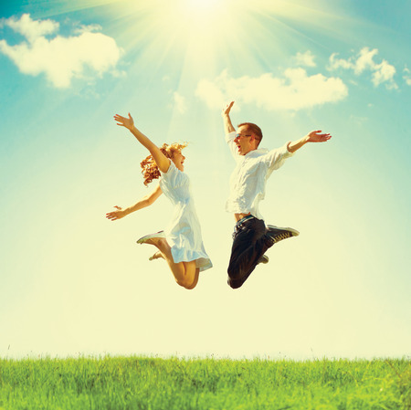 Foto de Happy couple outdoor. Jumping family on green field - Imagen libre de derechos