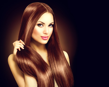 Beautiful brunette woman touching her long shiny straight hair