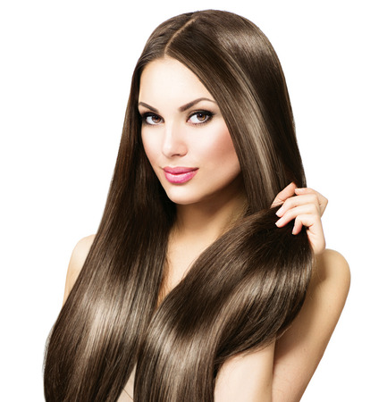 Foto de Beautiful brunette woman touching her long shiny straight hair - Imagen libre de derechos