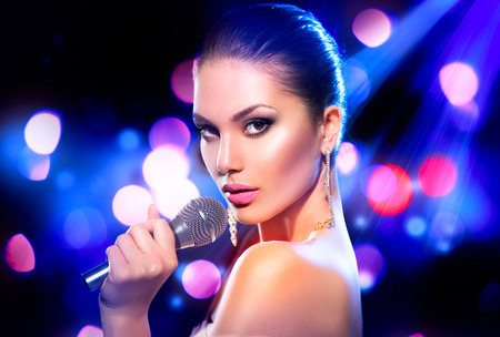 Photo for Woman with microphone over blinking bokeh night background - Royalty Free Image
