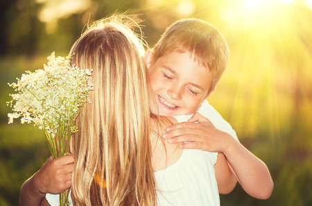 Photo pour Mother and her little son with bouquet of flowers outdoors - image libre de droit